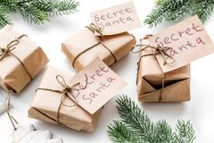 Secret Santa christmas game. Wrapped gift boxes with handwritten notes near spruce branch on white background close up Royalty Free Stock Photography