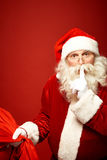 Secret of Santa. Santa Claus with sack of Christmas presents keeping forefinger by mouth royalty free stock photos