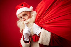 Secret of Santa. Santa with sack of xmas gifts asking for silence Royalty Free Stock Photography