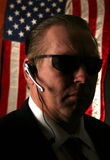 Secret service agent. A Secret Service Agent with a communication device in his ear in low light for a unique effect stock photography