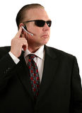 Secret service agent. A Secret Service Agent listens to instructions from his unseen boss isolated on white royalty free stock photography