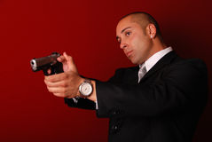 Secret service agent. Attractive man wearing a suit aiming a gun. Red background Stock Photo