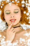 Secret smile with snowflakes. Christmas portrait of smiling redhead girl with snowflakes Stock Image