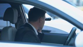 Secret spy in car looking through binoculars, confidential information search. Stock footage stock video footage