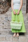 Secret on stairs. Young woman dressed in green with green handbag waits on stairs Royalty Free Stock Photography