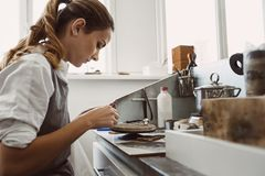 Secret technology. Side view of young female jeweler working on a new silver ring at her workbench. Jewelry making. Secret technology. e view of young female royalty free stock photography