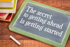 The secret to getting ahead concept. The secret to getting ahead is getting started - white chalk text on a slate blackboard with a stack of books against rustic Stock Photography