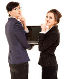 Secret, two young business women with laptop Royalty Free Stock Images