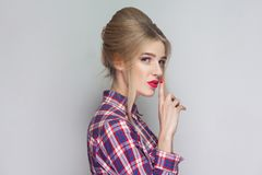 This is secret between us. beautiful girl in pink checkered shirt, collected updo hairstyle and makeup standing and looking at ca. Mera finger on her red lips royalty free stock photo