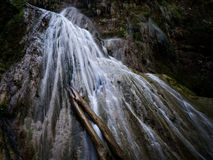 Secret waterfall with tree trunk. Santa Cruz, BOLIVIA in August 2015: Water from a river flows down a waterfall. The location of this waterfall in Eastern Royalty Free Stock Photo