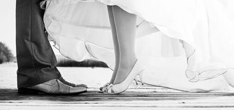 A secret wedding kiss. Legs of bride and groom standing on a bridge Royalty Free Stock Photo