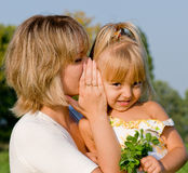 Secret whispers. Beautiful daughter listening to her mother's secret whispers Stock Image