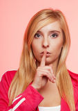 Secret woman. Fitness girl showing hand silence sign Royalty Free Stock Photography