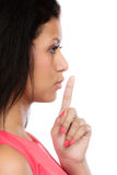 Secret woman. Girl showing hand silence sign. Secret woman finger on lips. Teen girl mixed race showing hand silence sign, saying hush be quiet. Face profile stock photo