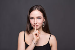 Secret. Young woman put finger on lips, hush sign Royalty Free Stock Images