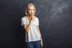 Secret. Young woman put finger on lips, hush sign Stock Photos