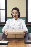 Secretaresse die een verrassingsdoos ontvangen op kantoor Stock Foto's