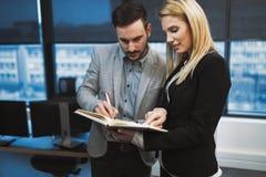 Secretaresse die werkgever in bureau helpen op het werk royalty-vrije stock afbeelding