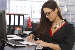 Secretaresse het schrijven nota's bij bureau Stock Foto's