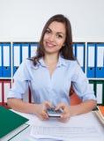 Secretaresse met lang donker haar en calculator op kantoor Stock Afbeeldingen