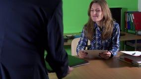 Secretaressevrouw die met tabletcomputer werken De cliëntmens brengt gebroken laptop stock videobeelden