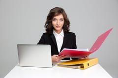 Secretaria bastante confiada que trabaja con el ordenador y las carpetas coloridas Imágenes de archivo libres de regalías