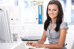 Secretaria bonita que pulsa en la sonrisa del ordenador Fotos de archivo