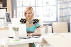 Secretaria casual que trabaja con el ordenador portátil Imagen de archivo libre de regalías