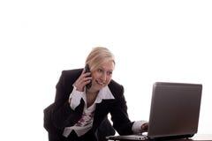 Secretaria con el teléfono y la computadora portátil Imagen de archivo