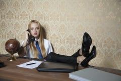 Secretaria con sus pies en el escritorio foto de archivo