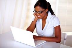 Secretaria de Chaming que hojea el Internet en la computadora portátil Imagen de archivo