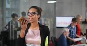 Secretaria de sexo femenino del africano joven que registra el mensaje audio metrajes