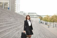 Secretaria de sexo femenino que se coloca en las escaleras con el bolso y los altos edificios en fondo Foto de archivo libre de regalías