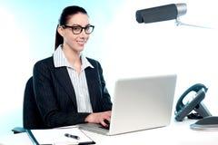 Secretaria de sexo femenino sonriente que trabaja en la computadora portátil Fotos de archivo