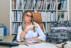 Secretaria enojada con la pila de las carpetas en la mesa Imagen de archivo