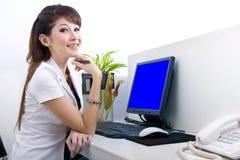 Secretaria hermosa con la pantalla de ordenador en blanco Imagen de archivo