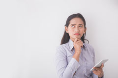 Secretaria joven asiática que piensa mientras que sostiene un teléfono móvil Whi Imagenes de archivo