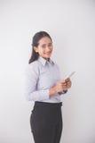 Secretaria joven asiática que sonríe mientras que sostiene un teléfono móvil B blanco Foto de archivo
