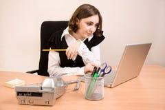Secretaria joven con el teléfono, computadora portátil fotografía de archivo