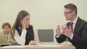 Secretaria joven del retrato que se sienta con su jefe en la oficina El hombre que corrige el informe de la muchacha Vida de la o almacen de metraje de vídeo