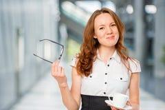 Secretaria joven delgada con los vidrios y el café foto de archivo libre de regalías