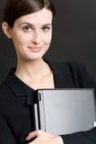 Secretaria o empresaria en juego con el cuaderno en fondo azul Imagen de archivo