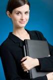 Secretaria o empresaria en juego con el cuaderno en fondo azul Imagen de archivo libre de regalías