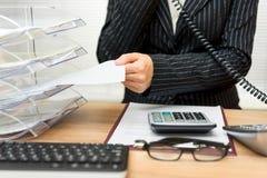 Secretaria ocupada con llamada de teléfono y carpetas con los ficheros Fotografía de archivo libre de regalías