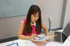 Secretaria que comprueba los detalles del informe de ventas imagen de archivo libre de regalías