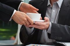Secretaria que sirve un café a su jefe Imagenes de archivo