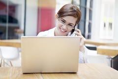 Secretaria que usa el teléfono celular con la computadora portátil Imagenes de archivo