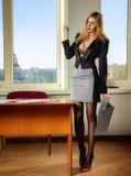 Secretaria sexual rubia en oficina con el ordenador portátil a disposición Foto de archivo