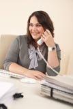 Secretaria sonriente en el teléfono en la oficina imagen de archivo libre de regalías