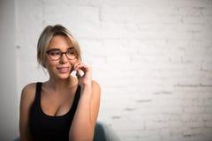 Secretaria sonriente encantadora de la mujer que habla en el teléfono móvil durante rotura de trabajo en compañía Imagen de archivo